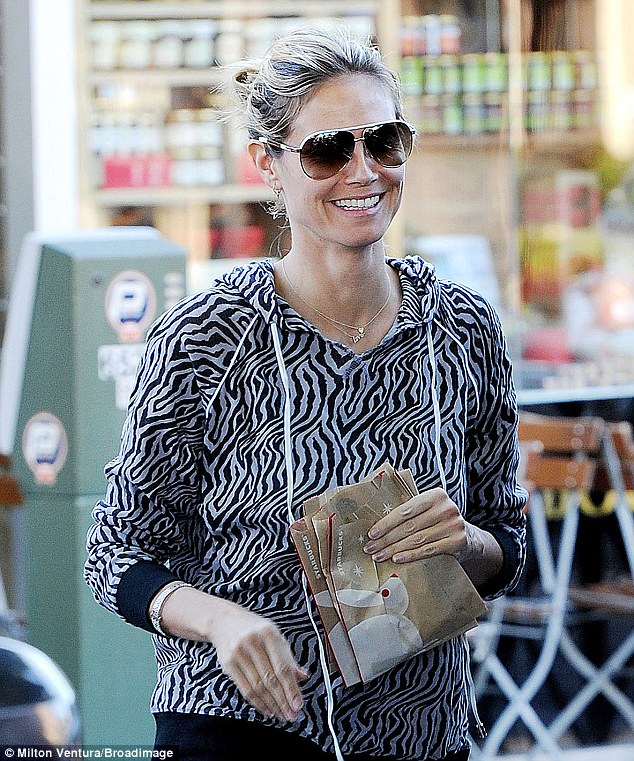 Make-up free: The former Victoria's Secret angel could not stop smiling as she returned to the car holding three bags of baked goodies