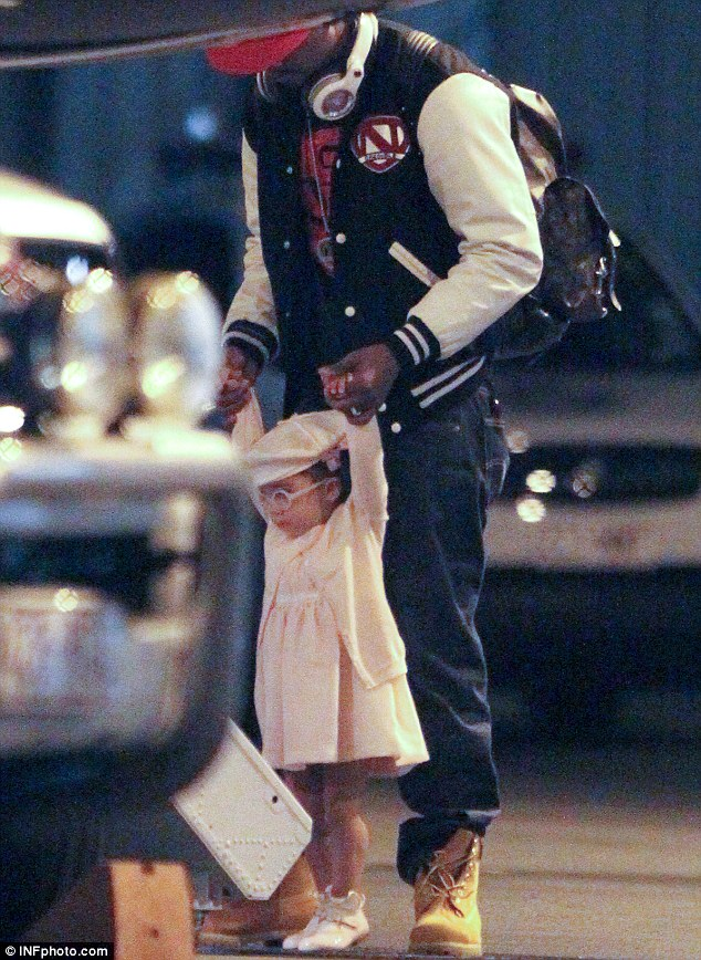 Daddy's little princess: Monroe looked positively adorable in her baby pink ensemble as he helped her onto the plane