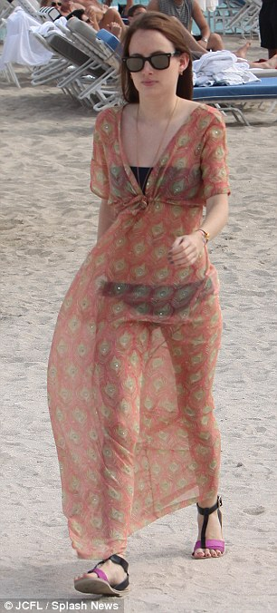 Beach style: Rosie still even managed to look stylish as she covered up in a sheer orange slip after calling it a day