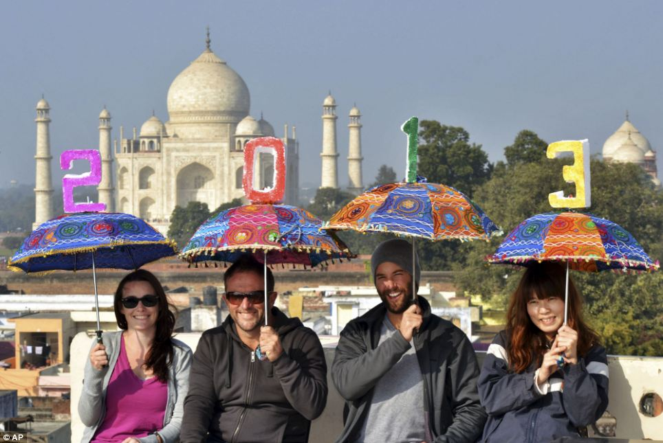 Tourists pose as they carry umbrellas with numbers to welcome the New Year 2013 on the terrace of a hotel in the backdrop of Taj Mahal in Agra, India