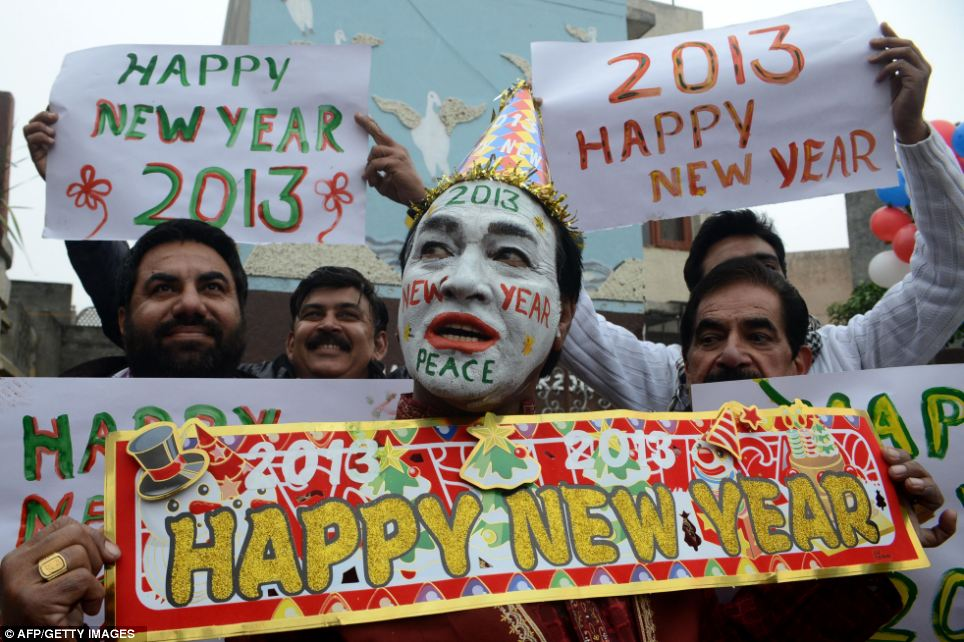 Indian revellers hold placards in Amritsar saying 'happy New Year'