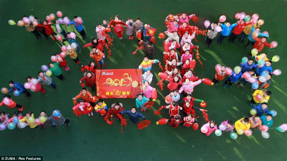 Pupils stand to form the shape of '2013' as they wait for the arrival of the new year at Jiujiang Elementary School in Jiangxi Province, China