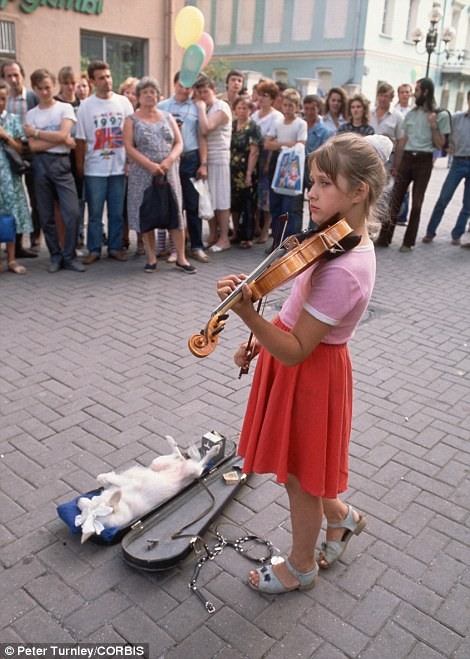 A young girl plays her violin for a crowd on Moscow's Arbat Street with her dog lounging in the violin case