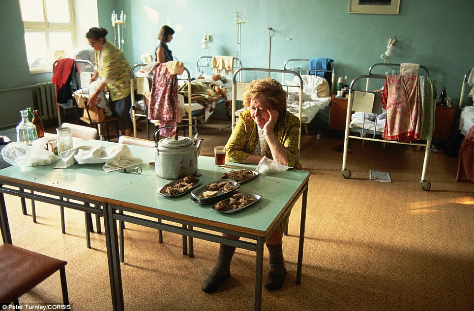 Looks more like the 1970s: Women patients sit at a table with food and fold their laundry in a rundown hospital ward in Moscow in July 1991