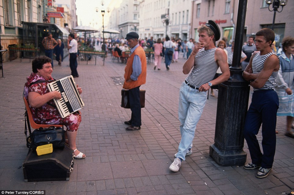 Getting by: A woman plays her accordion along Arbat Street in Moscow, a popular pedestrian thoroughfare, as several men stand nearby watching her
