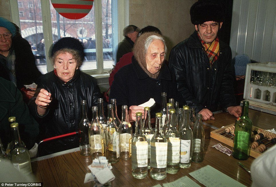 Small comfort: Women stand next to several empty vodka bottles in bar in Moscow, showing that there was still money around for some products