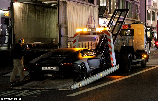 Away we go: Mr Al Rashed's Lamborghini Aventador supercar is taken away by police as a cameraman films