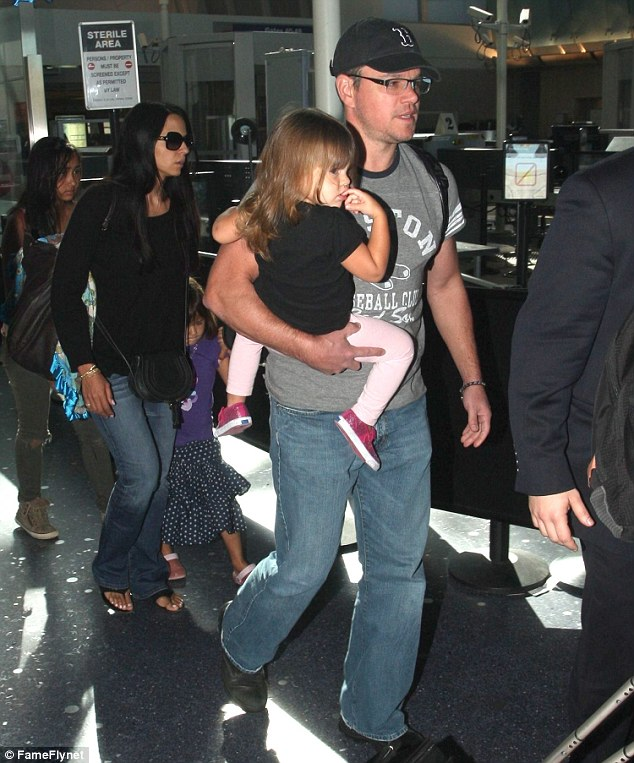 Keeping her close: Matt held on tightly to his daughter as he arrived at LAX