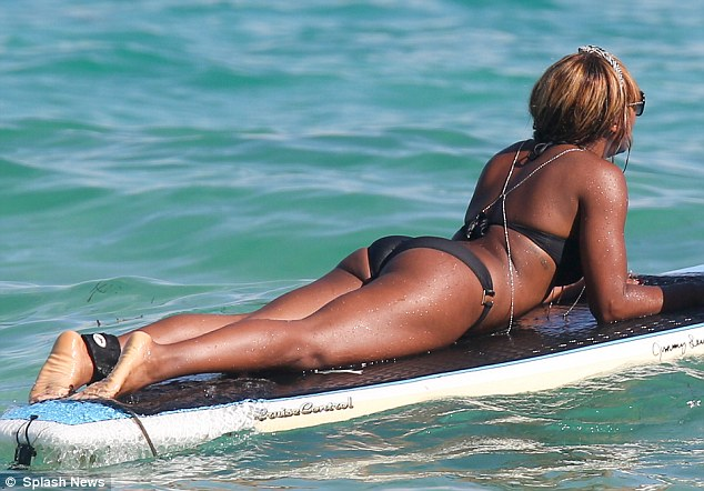 Relaxing: Why paddle when you can just chill? Alexandra shows off her amazing figure as she glides through the ocean