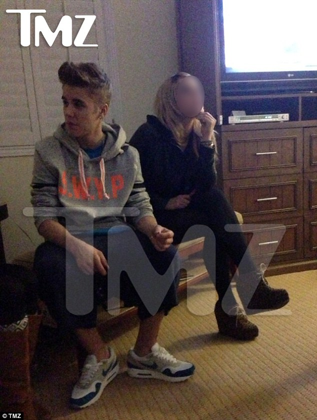 Mystery friend: Justin was snapped sitting next to a woman and later a girl is said to have slept in his room