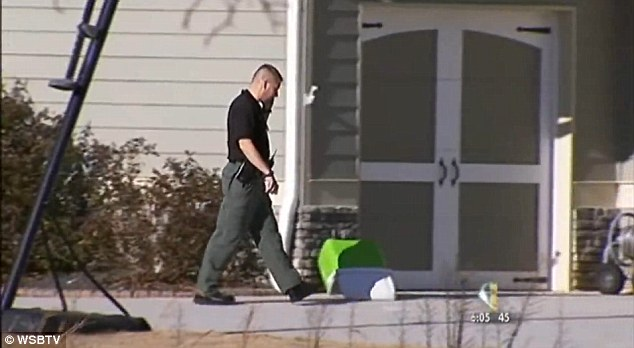 Investigation: A sheriff's deputy is pictured outside the home following the shooting on Friday