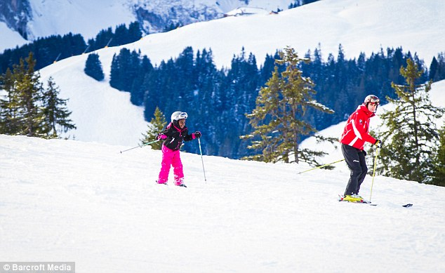 Having a ball: Mercy was clearly really enjoying her time on the slopes, grinning as she was guided by an instructor