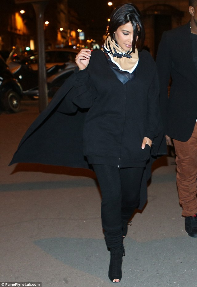 Batgirl! Kim Kardashian looks set to take flight as her huge cape is caught by the wind on trip to Paris with Kanye West on Tuesday