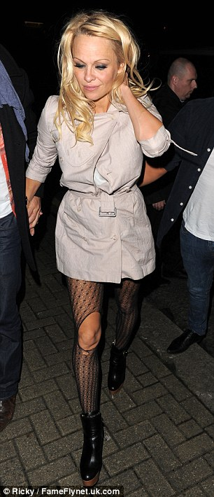 Not so sleek: After partying the night away Pamela re-emerged from the club with ripped tights and messy hair