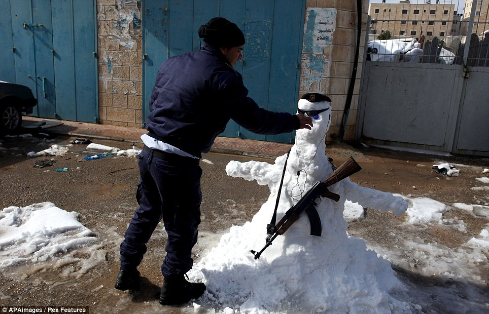 A Palestinian policeman shirks the usual decoration to dress his snowman in the West Bank city of Ramallah