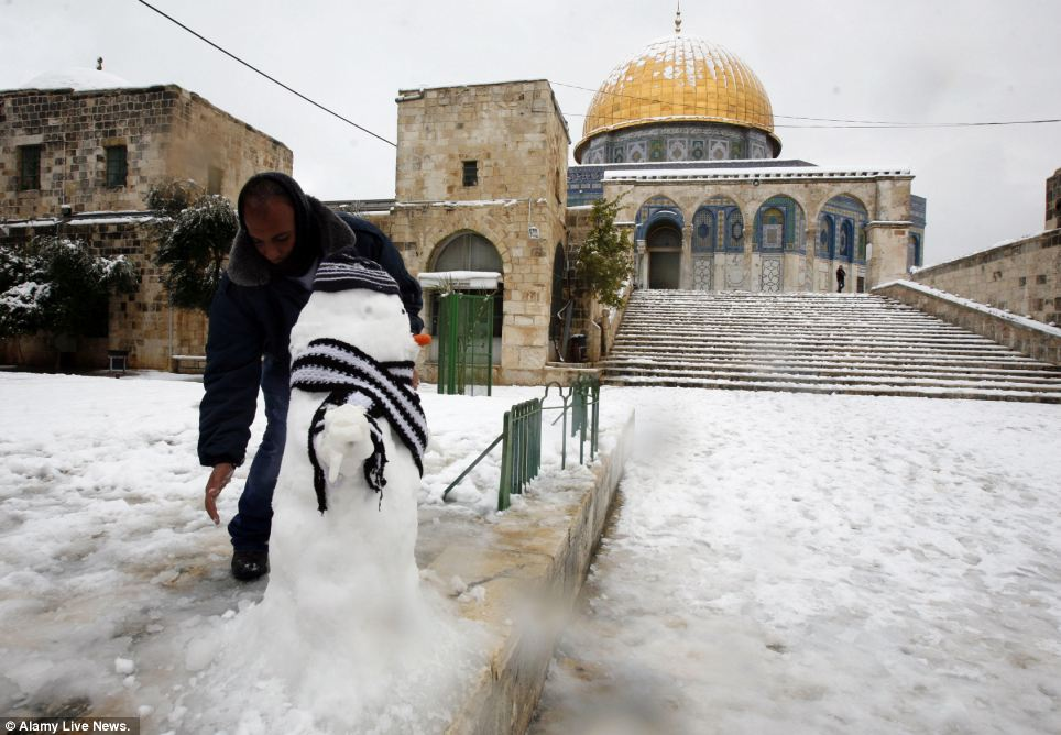 A Palestinian builds a snowman in the old city of Jerusalem - and even adds a hat and scarf to keep the figure warm