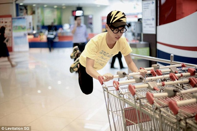 Shop till you drop: A young man holds on for dear life as he appears to be floating away from a trolley