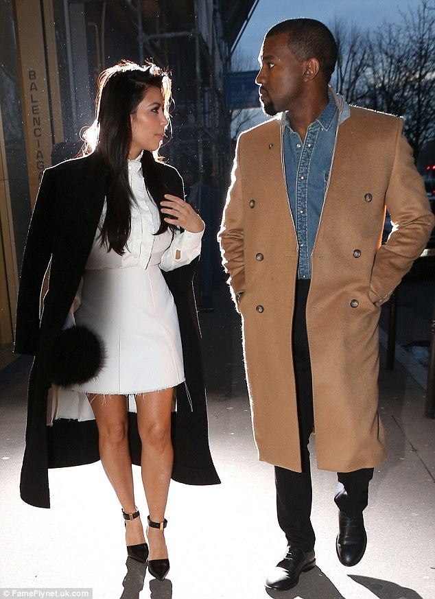 Edgy: Meanwhile, Kanye also kept warm in a beige lapel-less overcoat, which he wore over a pair of black trousers and a denim shirt