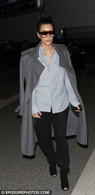 Dowdy: Kim's outfit consisted of a grey overcoat, pin-striped blue blouse and black trousers, but the peek-a-boo black heels were one bright spot