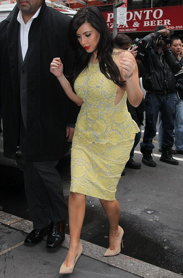 All in yellow: Kim Kardashian shows off her pregnancy curves in a clinging floral dress as she arrives to film Live With Kelly And Michael in New York on Tuesday morning