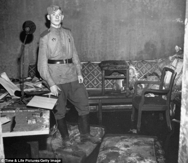 On guard: Russian soldier standing amid rubble in Adolf Hitler's command bunker