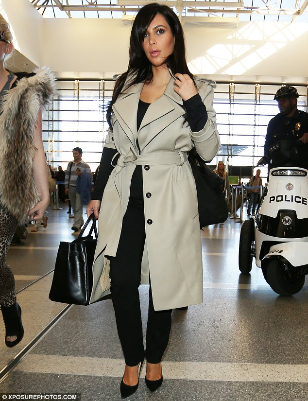 Perfecting her pout: Kim tossed her hair for the cameras when she arrived at LAX airport
