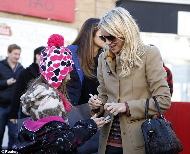 Young fan: Naomi Watts wore a camel-coloured coat over her striped jumper and jeans while signing autographs in Park City