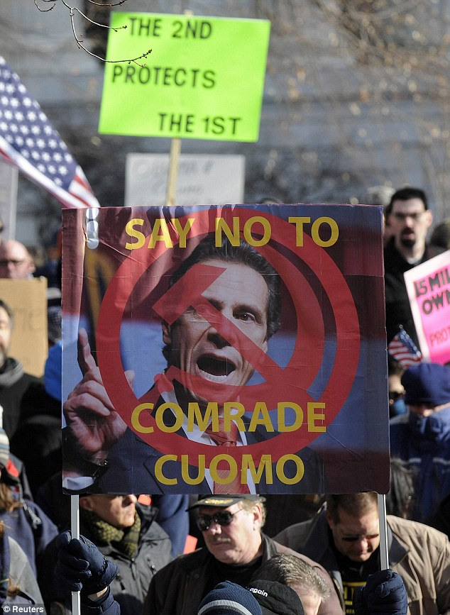 Attacks: A protestor holds a sign showing Gov Andrew Cuomo's face, four days after he signed the nation's toughest assault weapon and magazine restrictions for the state