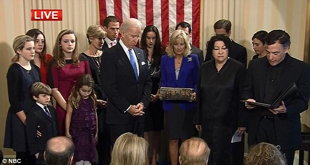 Religious touch: Reverend Kevin O'Brien (right), who is a member of the faculty at Georgetown University, gave a blessing before Mr Biden took the oath of office