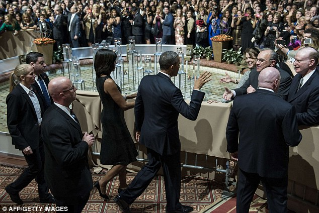 Walk this way: Flanked by their security detail, the Obamas attend an inauguration reception