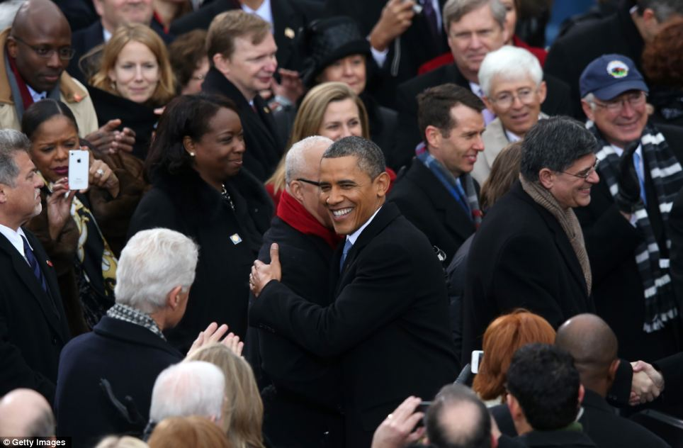 Welcome: President Barack Obama arrives during the presidential inauguration and embraces supporters as Bill Clinton looks on