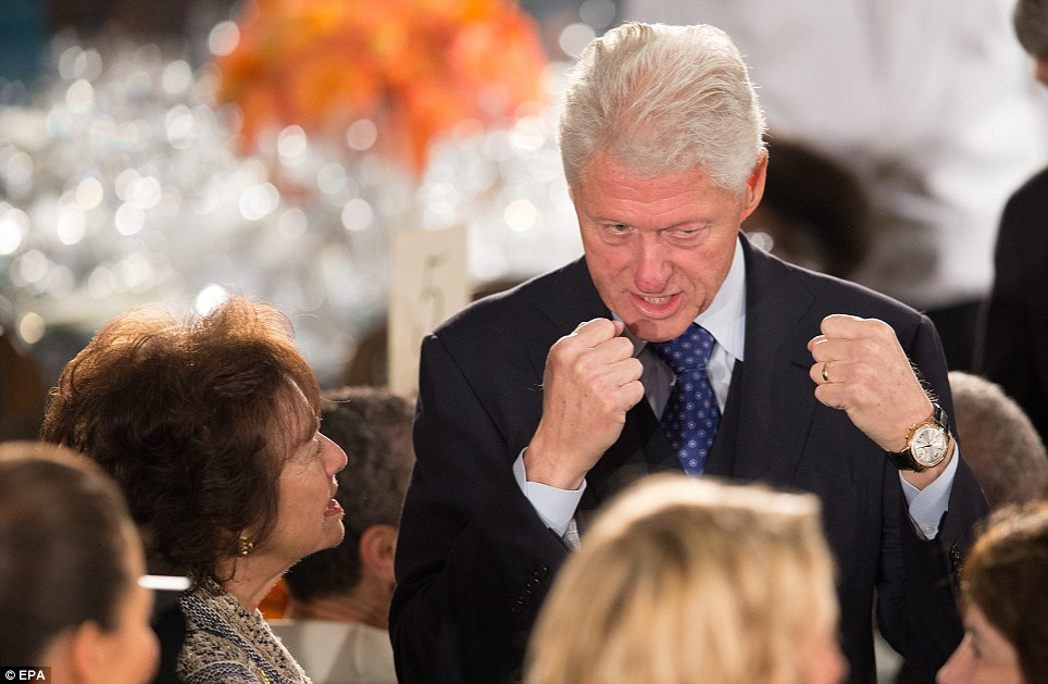 High spirits: Bill Clinton puts his fists up as he jokes around at the inaugural lunch inside the Capitol building on Monday afternoon