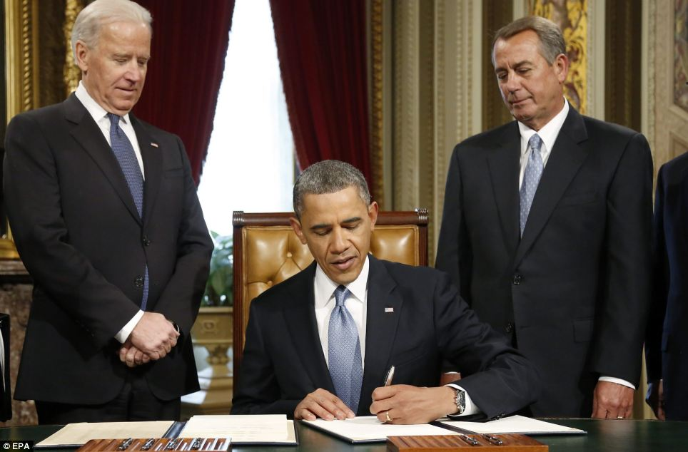 Signature: President Obama signs a proclamation to commemorate the inauguration, entitled a 'National Day of Hope and Resolve', flanked by Biden and House Speaker John Boehner
