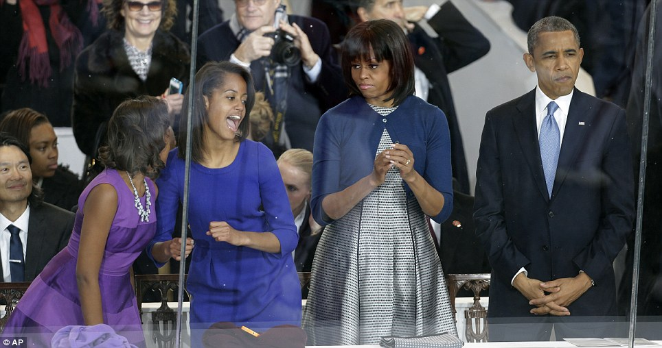 Clowning around: The Obama girls dance while Michelle and Barack stay serious as they watch the parade from the presidential box