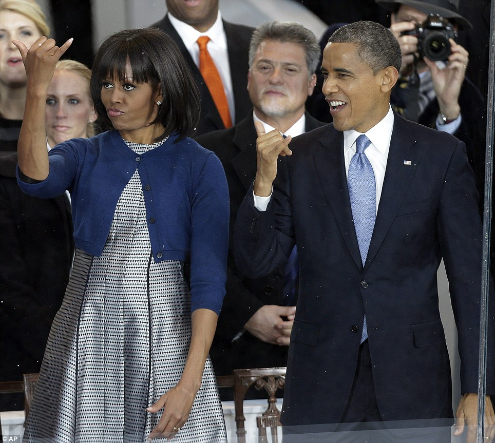 Aloha! Barack and Michelle greet the Hawaii home state float on Monday with the shaka sign meaning 'hang ten'