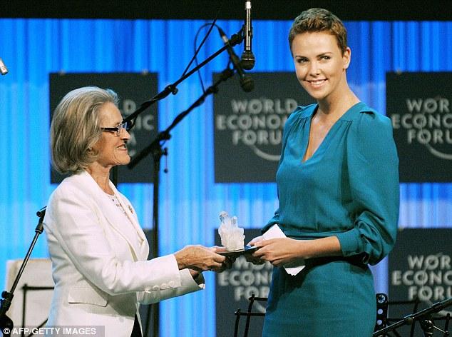 Honoured: Charlize receives a World Economic Forum Crystal award from Hilde Schwab, of the Schwab Foundation for Social Entrepreneurship