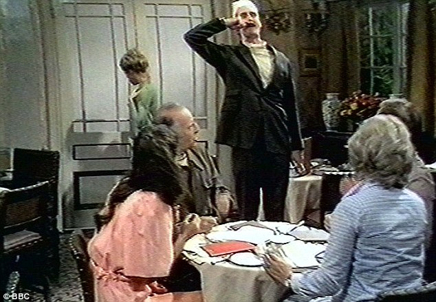 'Don't mention the war': John Cleese as Basil Fawlty giving an Adolf Hitler impression to German guests, with Polly in the background played by Connie Booth