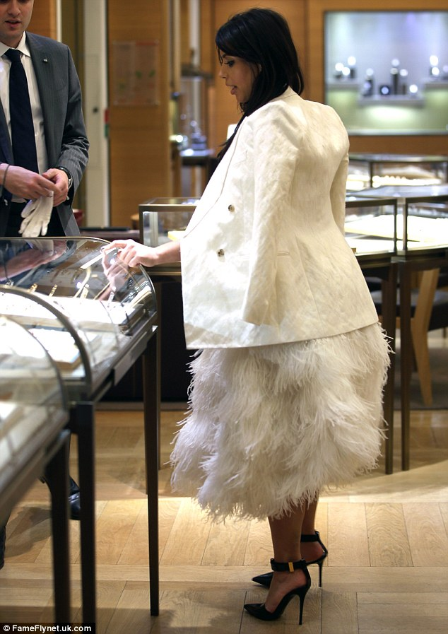 Ruffling feathers: Pregnant Kim Kardashian stepped out in a giant white feathered ball gown as she went shopping with Kanye West in Paris on Friday