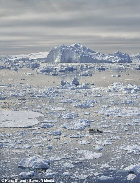 Fishermen steer their boat close to a giant iceberg in Disko Bay, Greenland