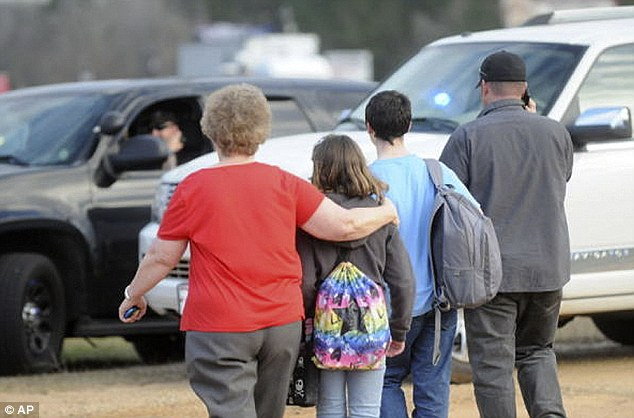 Safe: Parents hugged their children tightly after the ordeal on the bus. Witnesses say the gunman was looking for a hostage because of his legal trouble