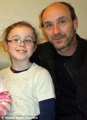 John Clarke, father of deaf schoolgirl Hafwen (pictured together) is threatening to sue his local council because his daughter has a right to a Welsh sign language expert