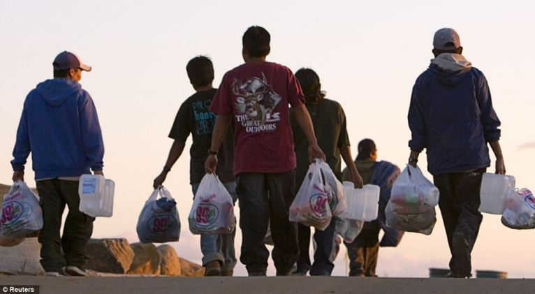 Long day: In San Diego, a group of migrant farm workers walk back to their camp with food, clothing and other supplies donated to them near the fields where they pick fruit
