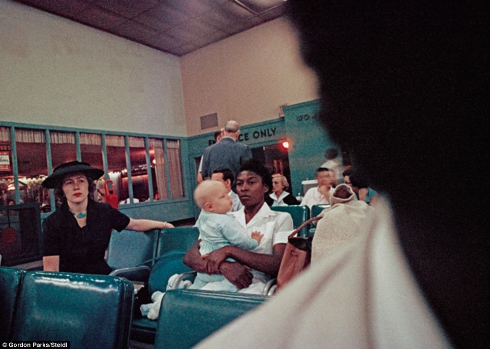 Caring: An African American maid grips hold of her young charge in a waiting area as a smartly-dressed white woman looks on