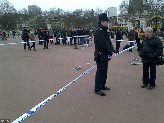 Police standing guard: A cordoned off area containing knives, a hat and taser wire outside Buckingham Palace