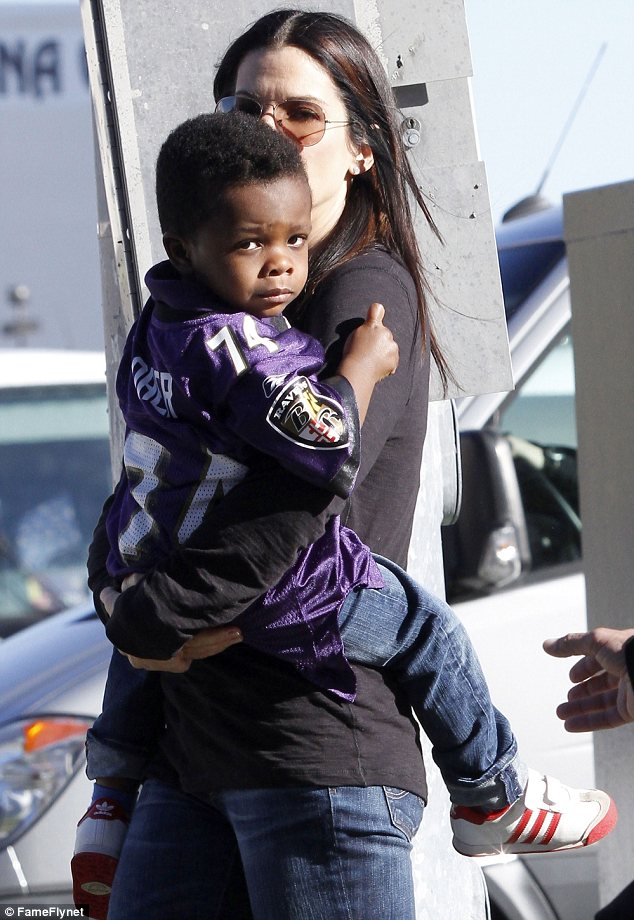 Proud mama: Sandra dressed her son, Louis, in a Michael Oher jersey as they attended the Super Bowl on Sunday