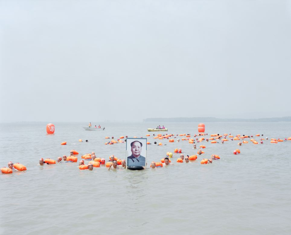 Zhang Kechun's series of photographs was inspired by the novel River of the North by Zhang Chengzhi. This photograph shows swimmers crossing the Yellow River holding a picture of Mao
