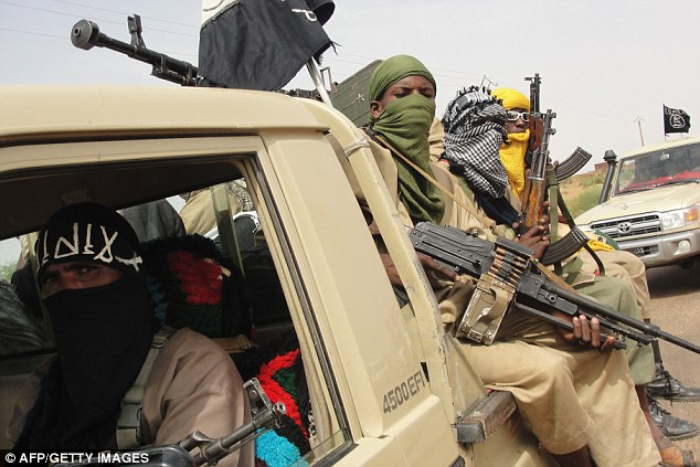 ARMED WITH MACHINE GUNS. ISLAMO-NAZIS WEARING THE BLAG FLAG OF JIHAD.Members of the al-Qaeda-linked terror group Ansar Dine Islamist ride in the back of a pick-up truck. Now three captured fighters claim to have been tortured by Malian soldiers using waterboarding following the liberation of Timbuktu (file picture)