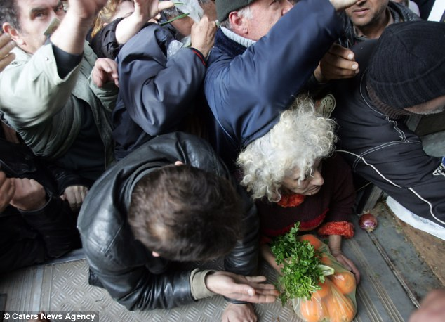Dire situation: An elderly woman holds on to a bag of oranges as she is nearly elbowed in the back of her head outside the Agriculture Ministry in Athens