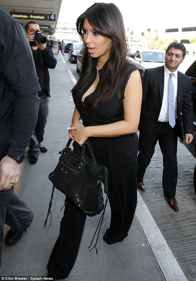 Taking flight: Kim arrives at the airport in Los Angeles where she caused a media frenzy