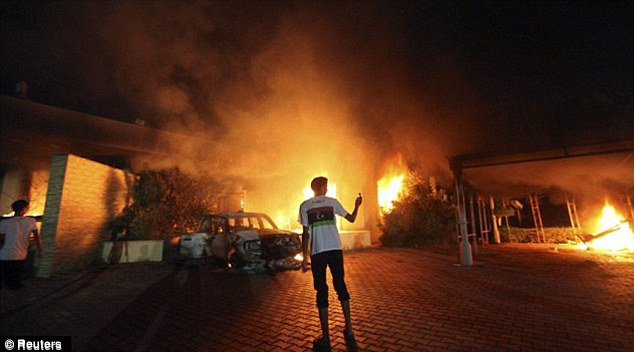 Under attack: An armed man waves takes a picture as buildings and cars are engulfed in flames after being set on fire inside the US consulate compound in Benghazi late on September 11